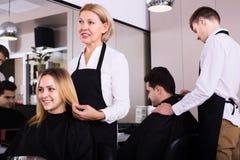 Mogen frisör som arbetar på salongen Fotografering för Bildbyråer
