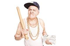 Mogen gangster som rymmer ett slagträ och pengar arkivbild