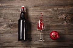 Mogen granatäpplefrukt med ett exponeringsglas av vin, en flaska på en träbakgrund royaltyfri foto