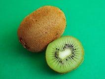 Mogen hel kiwi och halv kiwi som isoleras på grön bakgrund royaltyfria foton