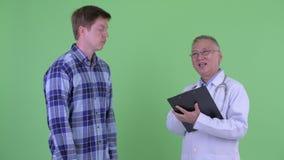 Mogen japansk mandoktor med den unga mannen som har konsultation för sjukdom lager videofilmer
