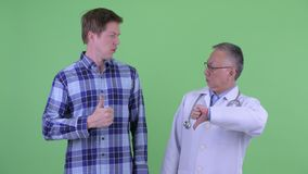 Mogen japansk mandoktor med den unga mannen som har olika åsikter tillsammans lager videofilmer