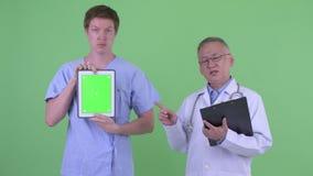 Mogen japansk mandoktor med patienten för ung man som visar den digitala minnestavlan och förklarar något lager videofilmer