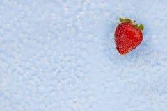 Mogen jordgubbe i blått vatten med luftbubblor arkivfoton