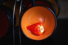 Mogen jordgubbe i en orange kopp på en kopphållare i en svart b arkivfoton