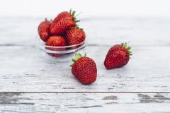 Mogen jordgubbe som ligger i hög på trätabellen Arkivbilder