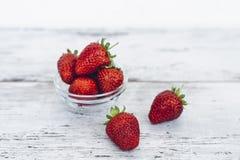 Mogen jordgubbe som ligger i hög på trätabellen Royaltyfri Bild