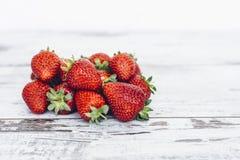 Mogen jordgubbe som ligger i hög på trätabellen Fotografering för Bildbyråer