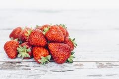 Mogen jordgubbe som ligger i hög på trätabellen Royaltyfri Fotografi