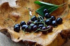 Mogen körsbär i en trävas Träbunke med mogna körsbär arkivfoto