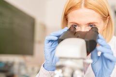 Mogen klinisk forskare som använder mikroskopet arkivbild