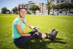 Mogen kvinna för passform i rullblad på gräset Arkivfoto