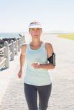 Mogen kvinna för passform som joggar på pir Arkivfoton