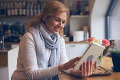 Mogen kvinna för Smiley som använder den digitala minnestavlan i kafé Arkivbild