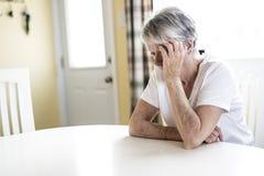 Mogen kvinna hemma som trycker på hennes huvud med henne händer, medan ha en huvudvärk smärta royaltyfria bilder