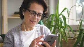 Mogen kvinna i exponeringsglas och hörlurar som bläddrar skärmen arkivfilmer