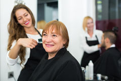 Mogen kvinna i frisersalongen Arkivfoton