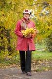 Mogen kvinna i höstpark Royaltyfria Foton