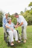 Mogen kvinna i rullstol med maken och dottern Arkivbilder
