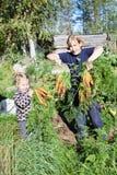 Mogen kvinna i trädgård med barnet Arkivfoto