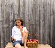 Mogen kvinna med äpplet och telefonen Royaltyfria Foton