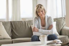 Mogen kvinna med armar korsat sammanträde på soffan royaltyfria foton