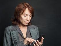 Mogen kvinna med att prata för smartphone royaltyfri foto