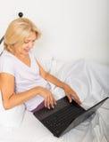 Mogen kvinna med bärbara datorn i säng Royaltyfri Bild