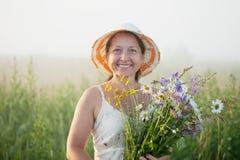 Mogen kvinna med blommaposyen Fotografering för Bildbyråer
