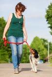 Mogen kvinna med den Brittany hunden på koppeln Fotografering för Bildbyråer