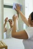 Mogen kvinna med den lokalvårdsprej och torkduken i badrum Arkivfoto