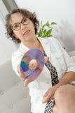 Mogen kvinna med en CD-SKIVA Arkivbilder