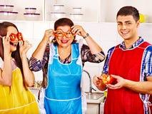 Mogen kvinna med familjen som förbereder sig på kök. Arkivfoto