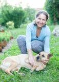 Mogen kvinna med hunden i gård Arkivfoto