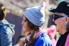Mogen kvinna med locket med det rosa bandet och råttsvansar som omges av andra suddiga kvinnor på Tulsa kvinnors mars i Tulsa Okl Royaltyfria Foton