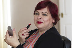 Mogen kvinna med spegeln och läppstift Fotografering för Bildbyråer