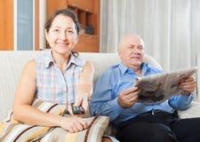 Mogen kvinna med TVfjärrkontrollen mot man med tidningen Arkivfoton