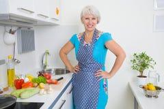 Mogen kvinna på kök Arkivfoto