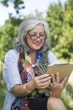 Mogen kvinna som använder den trådlösa apparaten Royaltyfria Bilder