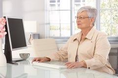 Mogen kvinna som använder datoren Arkivfoton