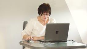 Mogen kvinna som arbetar med bärbara datorn Hon är iklädd en affärsdräkt och strikta exponeringsglas arkivfilmer