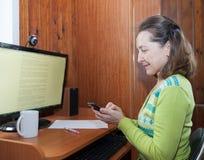 Mogen kvinna som arbetar nära datoren Fotografering för Bildbyråer