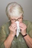 Mogen kvinna som blåser hennes näsa Arkivfoton