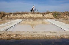 Mogen kvinna som cyklar bredvid den Isla Cristina saltworksen, Spanien Arkivbild