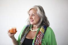 Mogen kvinna som dricker morotfruktsaft royaltyfria bilder