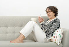 Mogen kvinna som dricker te på soffan Royaltyfri Foto