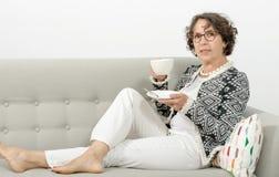 Mogen kvinna som dricker te på soffan Fotografering för Bildbyråer