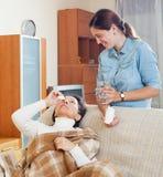 Mogen kvinna som dryper nasala droppar Arkivfoton