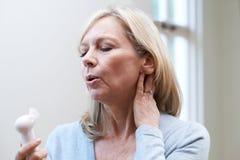 Mogen kvinna som erfar varm spolning från klimakterium arkivbild