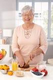 Mogen kvinna som förbereder den sunda frukosten Royaltyfri Foto